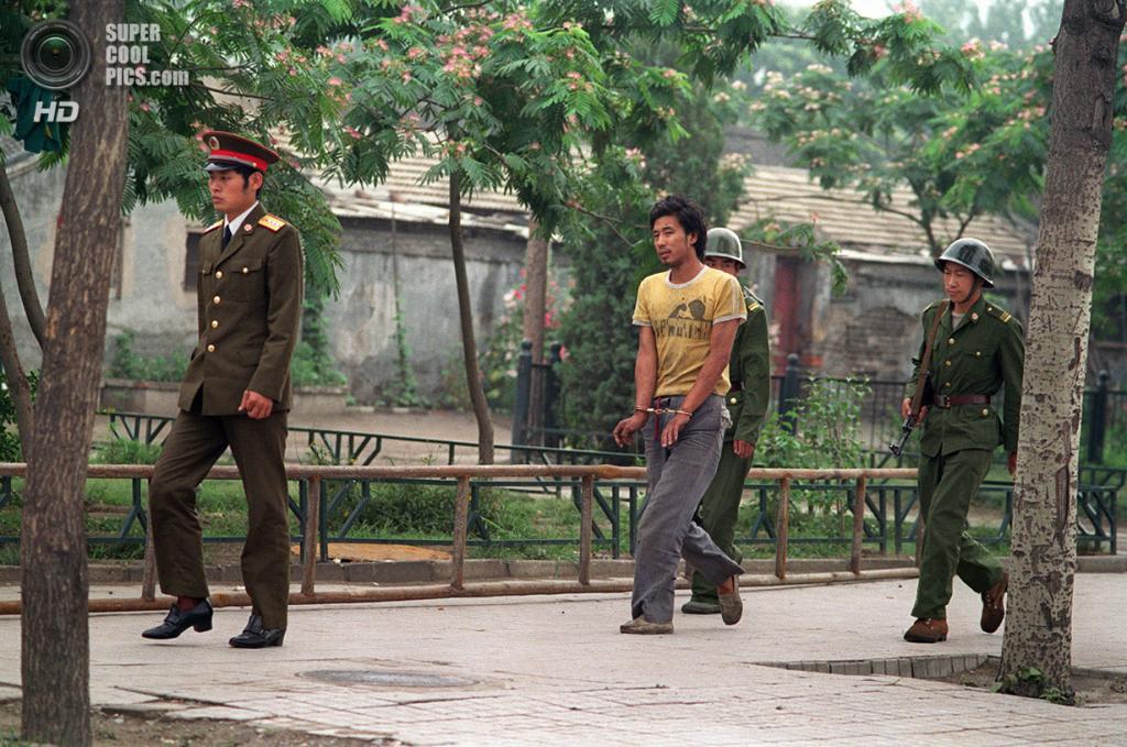 Китай. Пекин. 15 июня 1989 года. Солдаты ведут арестованного студента. Многих участников шестинедельного митинга отправили в тюрьму или расстреляли после показательных судов. (Manuel Ceneta/AFP/Getty Images)