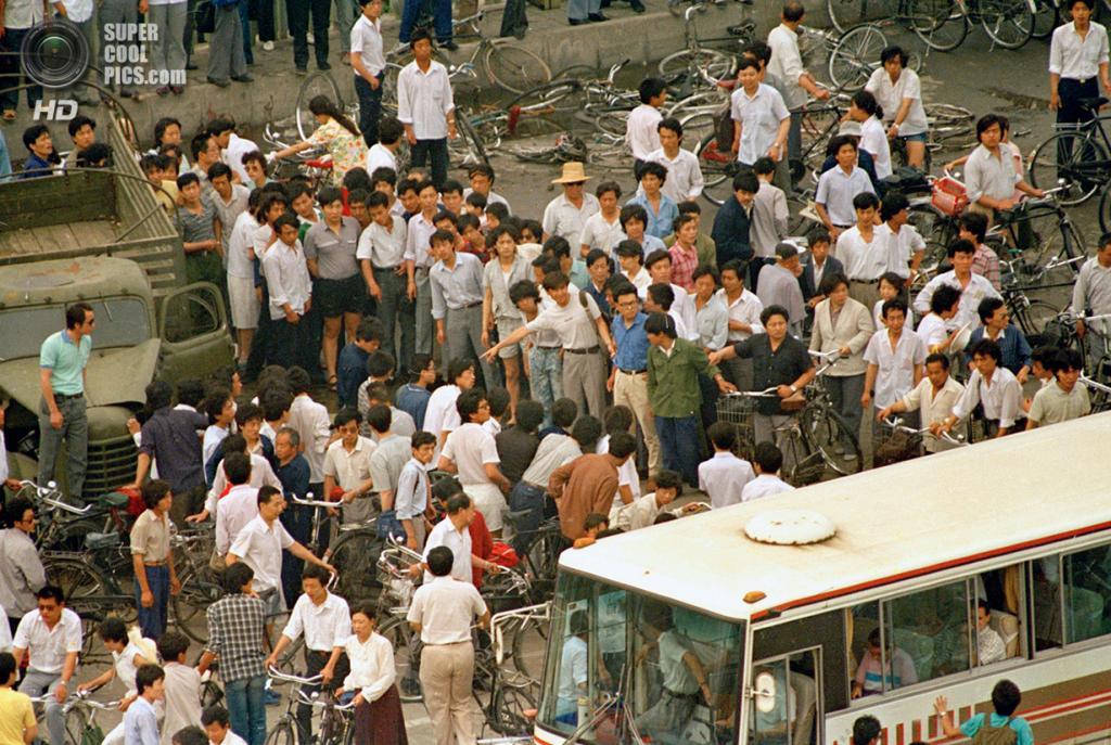 Китай. Пекин. 5 июня 1989 года. Люди расступаются перед автобусом с зарубежными туристами, чтобы показать им труп, оставшийся после событий 4 июня. (AP Photo/Mark Avery)