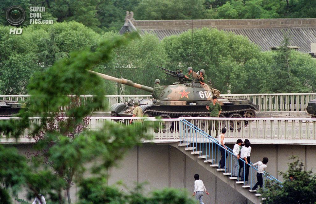 Китай. Пекин. 5 июня 1989 года. Прохожие разбегаются, после того как солдат наставил на них пистолет и приказал очистить улицу. (Catherine Henriette/AFP/Getty Images)