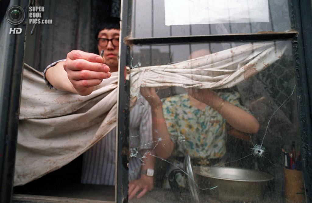 Китай. Пекин. 5 июня 1989 года. Мужчина демонстрирует пулю, пробившую окно его квартиры во время событий 4 июня на одной из улиц близ площади Тяньаньмэнь. (Manuel Ceneta/AFP/Getty Images)