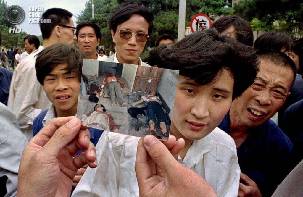 Китай. Пекин. 5 июня 1989 года. Люди на бульваре Сиань демонстрируют фотографию, якобы сделанную во время событий 4 июня. (AP Photo/Jeff Widener)