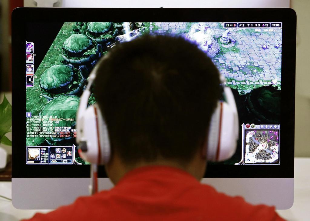 Китай. Пекин. 9 мая. Парень играет за компьютером в Интернет-кафе. (REUTERS/Kim Kyung-Hoon)