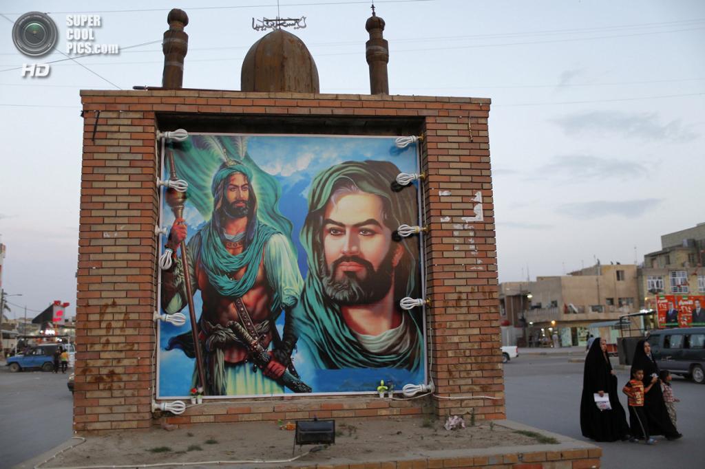 Ирак. Садр-Сити, Багдад. 1 мая. Шиитки проходят мимо огромного постера с имамом Хуссейном и имамом Аббасом. (REUTERS/Ahmed Jadallah)
