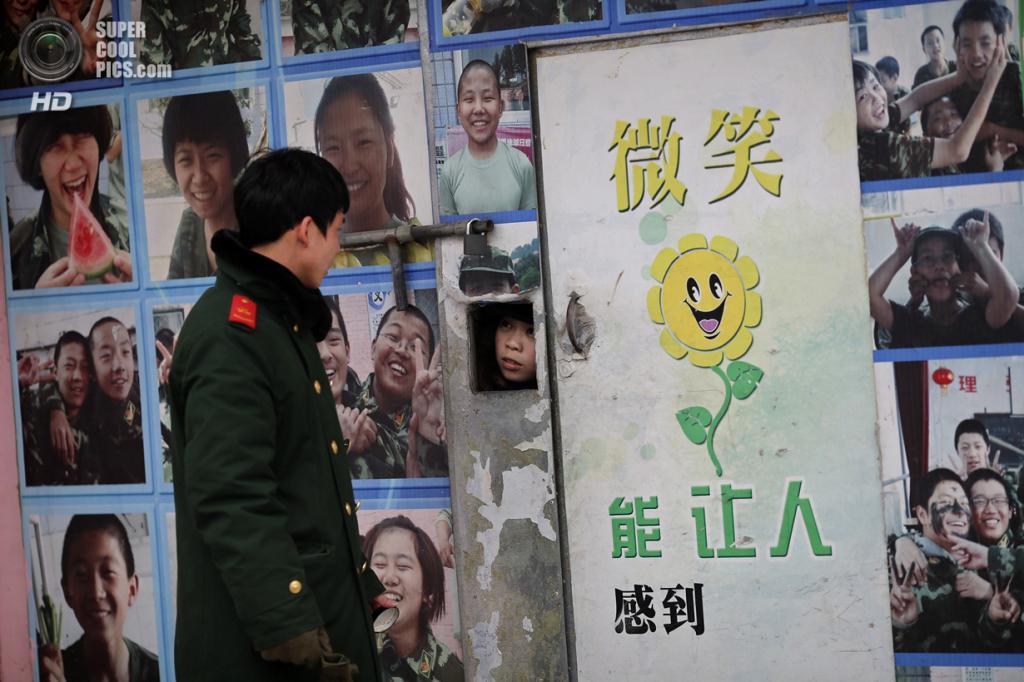 Китай. Пекин. 19 февраля. Вход в Учебный центр «Цидэ», обклеенный фотографиями счастливых подростков. (REUTERS/Kim Kyung-Hoon)