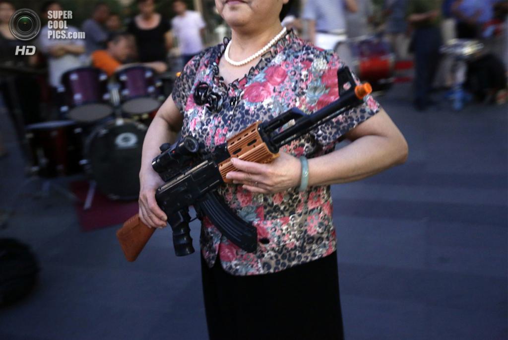 Китай. Пекин. 27 июня. Патриотические танцы с игрушечным оружием в исполнении местных жителей. (REUTERS/Jason Lee)