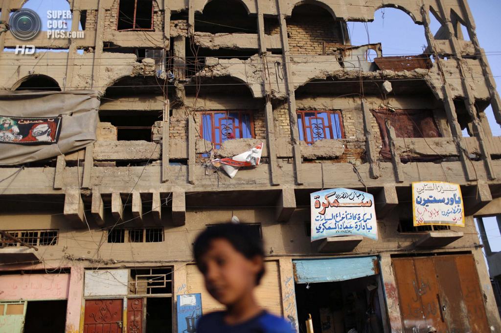 Ирак. Садр-Сити, Багдад. 3 мая. Мальчик на фоне здания, разрушенного в ходе войны в Персидском заливе. (REUTERS/Ahmed Jadallah)