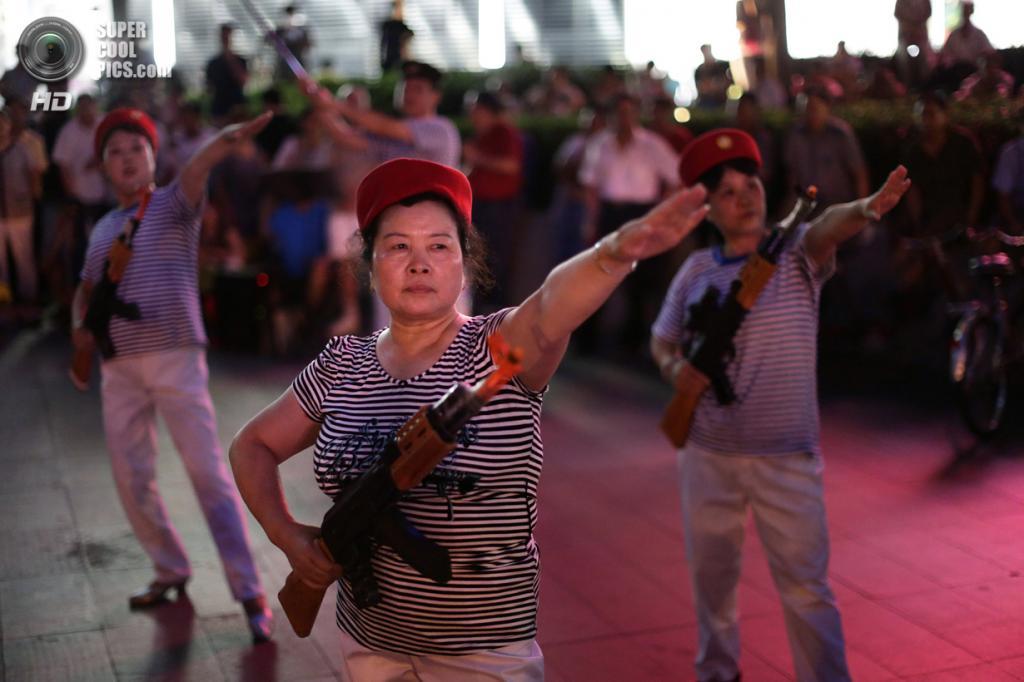 Китай. Пекин. 29 июня. Патриотические танцы с игрушечным оружием в исполнении местных жителей. (REUTERS/Jason Lee)