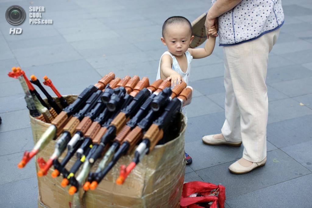 Китай. Пекин. 29 июня. Мальчишка рассматривает коробку с игрушечным оружием, используемым для танцев. (REUTERS/Jason Lee)