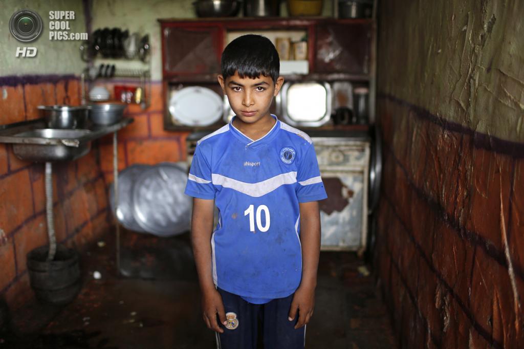 Ирак. Садр-Сити, Багдад. 3 мая. Слепой шиитский мальчик Хассун Каррус Хирмиз позирует для фото на кухне своего дома. (REUTERS/Ahmed Jadallah)