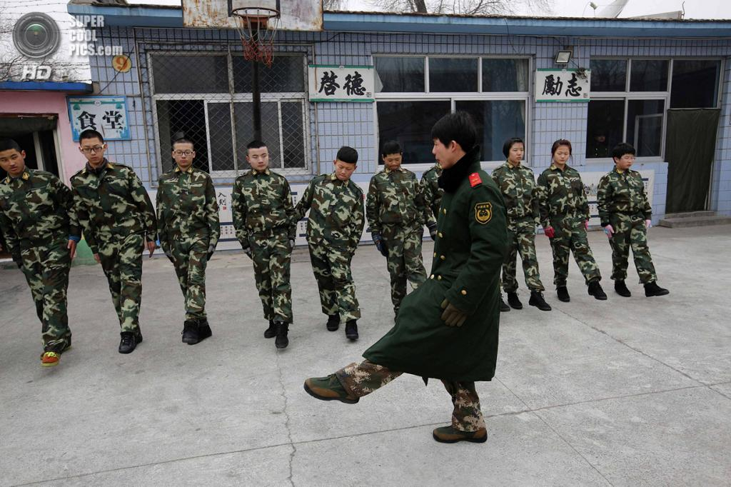 Китай. Пекин. 19 февраля. Инструктор учит курсантов строевому шагу. (REUTERS/Kim Kyung-Hoon)