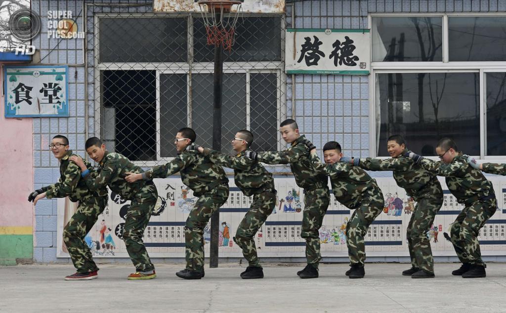 Китай. Пекин. 19 февраля. Курсанты смеются, получив наказание за невыполнение нормативов. (REUTERS/Kim Kyung-Hoon)