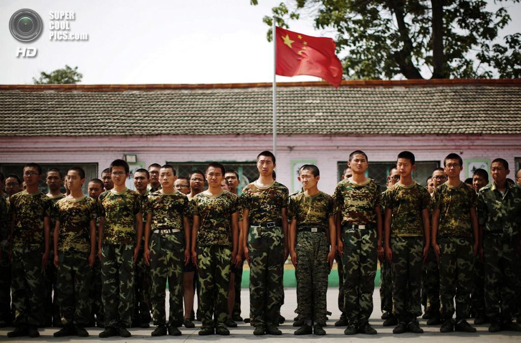 Китай. Пекин. 11 июня. Курсанты на фоне поднятого флага КНР. (REUTERS/Kim Kyung-Hoon)