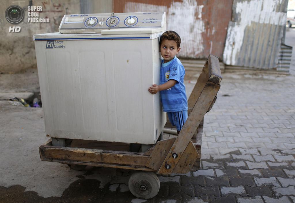 Ирак. Садр-Сити, Багдад. 29 апреля. Мальчик обнимает стиральную машину в тачке. (REUTERS/Ahmed Jadallah)
