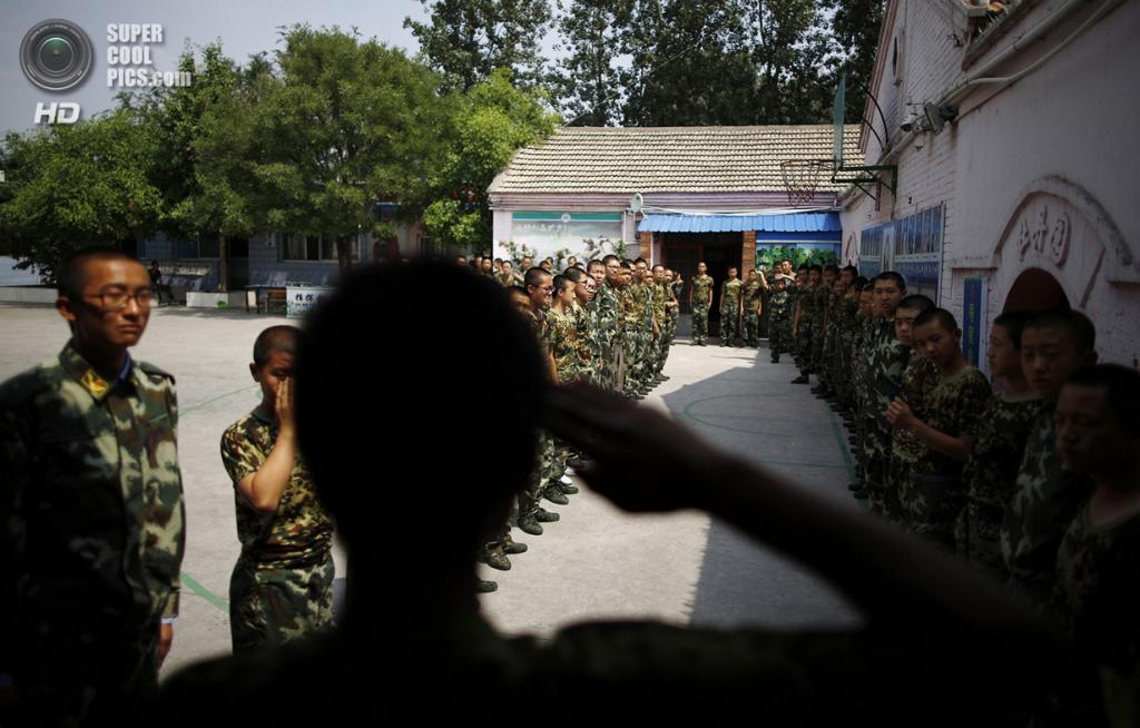 Китай. Пекин. 11 июня. Курсант, прошедший полный 6-месячный курс, салютует товарищам. (REUTERS/Kim Kyung-Hoon)