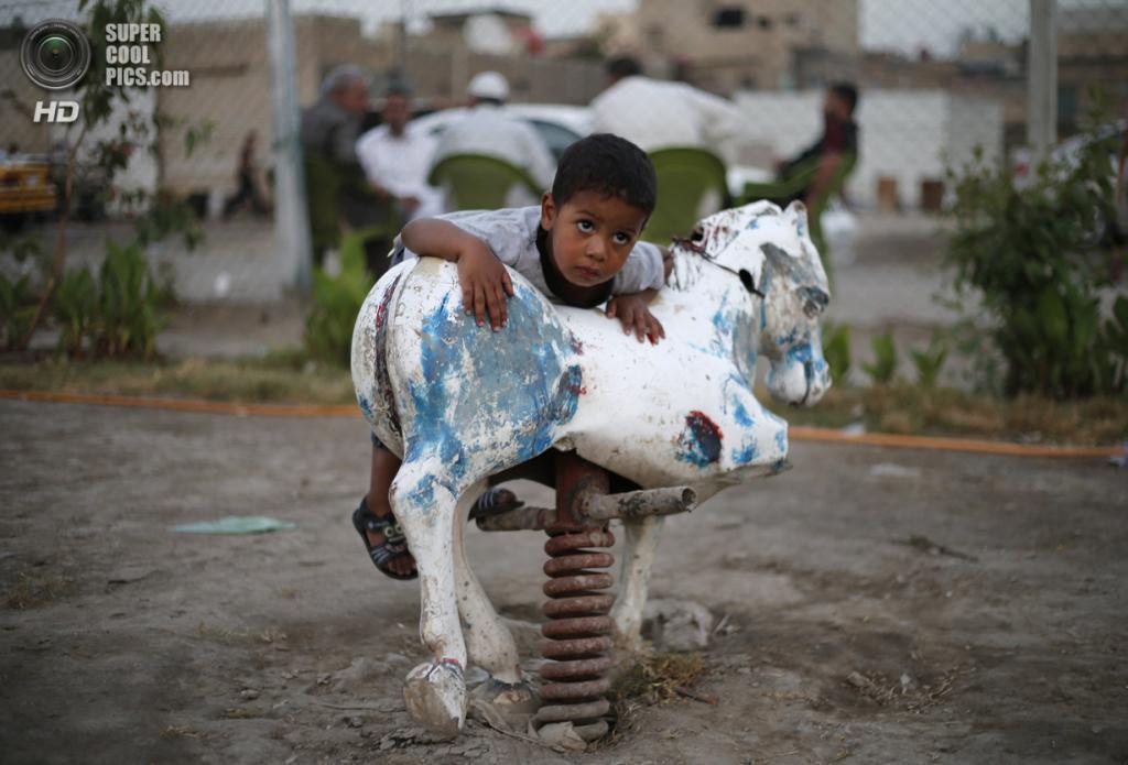 Ирак. Садр-Сити, Багдад. 27 апреля. Мальчик пытается взобраться на лошадку-качалку в парке. (REUTERS/Ahmed Jadallah)