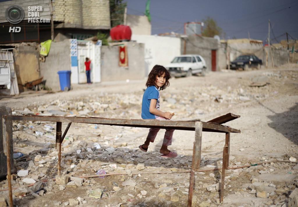 Ирак. Садр-Сити, Багдад. 5 мая. Девочка ест печенье, сидя на металлической лавочке. (REUTERS/Ahmed Jadallah)