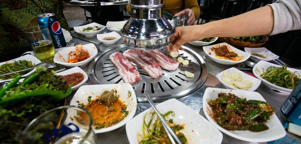 Самгёпсаль (кор. 삼겹살) — свиной бекон, который жарится на гриле, непосредственно на столах посетителей. Употребляется вприкуску со свежими листьями кунжута и салата. (Anton Diaz)
