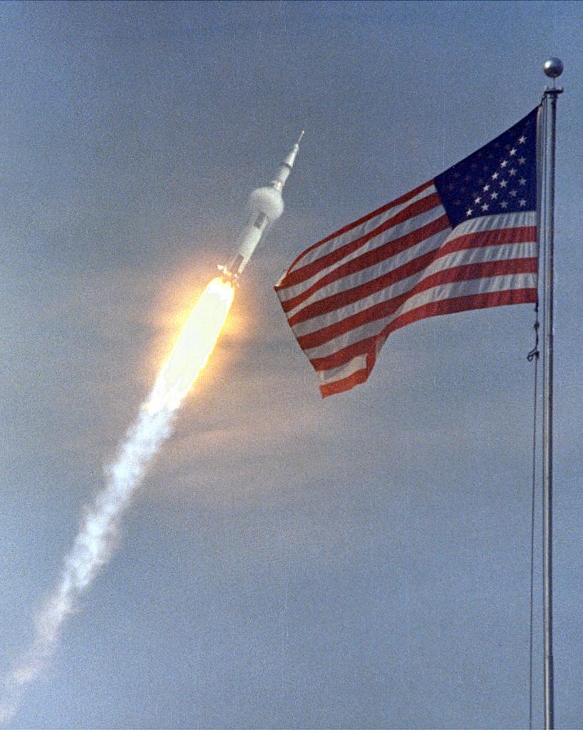 Американский флаг на фоне запуска миссии «Аполлон-11», которая совершила первую в истории человечества пилотируемую посадку на поверхность другого небесного тела. (NASA on The Commons)