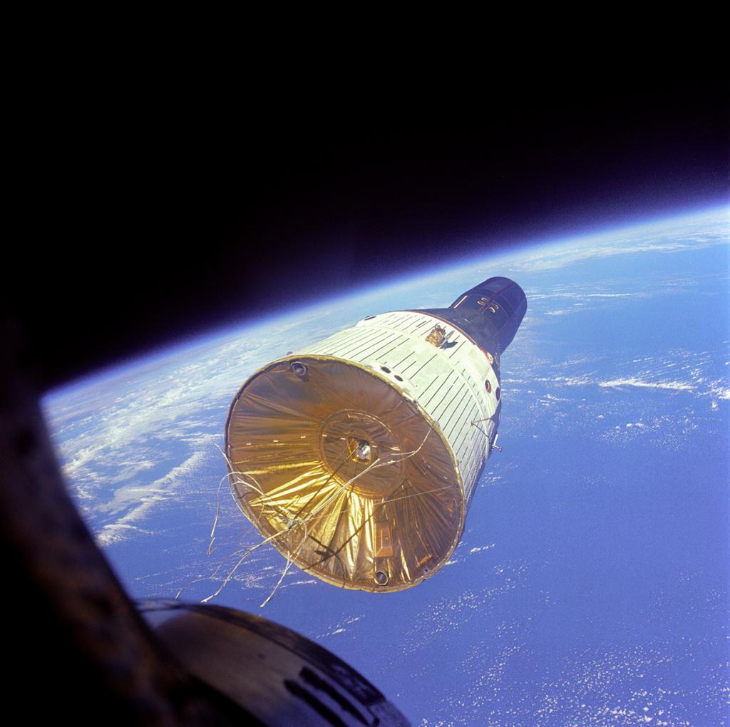 Вид на американский пилотируемый космический корабль «Джемини-7» с иллюминатора американского пилотируемого космического корабля «Джемини-6A». В момент сьёмки расстояние между объектами составляло 7 метров. На снимке «Джемини-7» находится на высоте 257 км над поверхностью Земли. (NASA on The Commons)