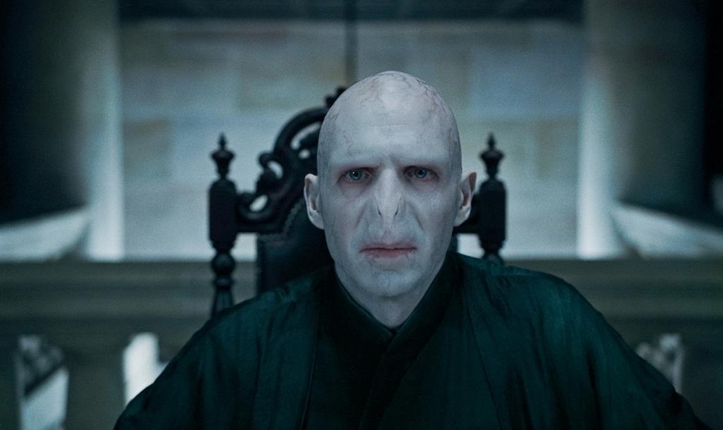 Большинство зрителей даже не догадывается, что Рэйф Файнс исполнил роль главного злодея в фильмах о Гарри Поттере. Для образа Волан-де-Морта актёру приходилось ежедневно брить голову, носить зубные протезы, накладные пальцы. Каждый раз перед сьёмками над ним работали профессиональные визажисты в течение трёх часов. (Кадр из фильма)