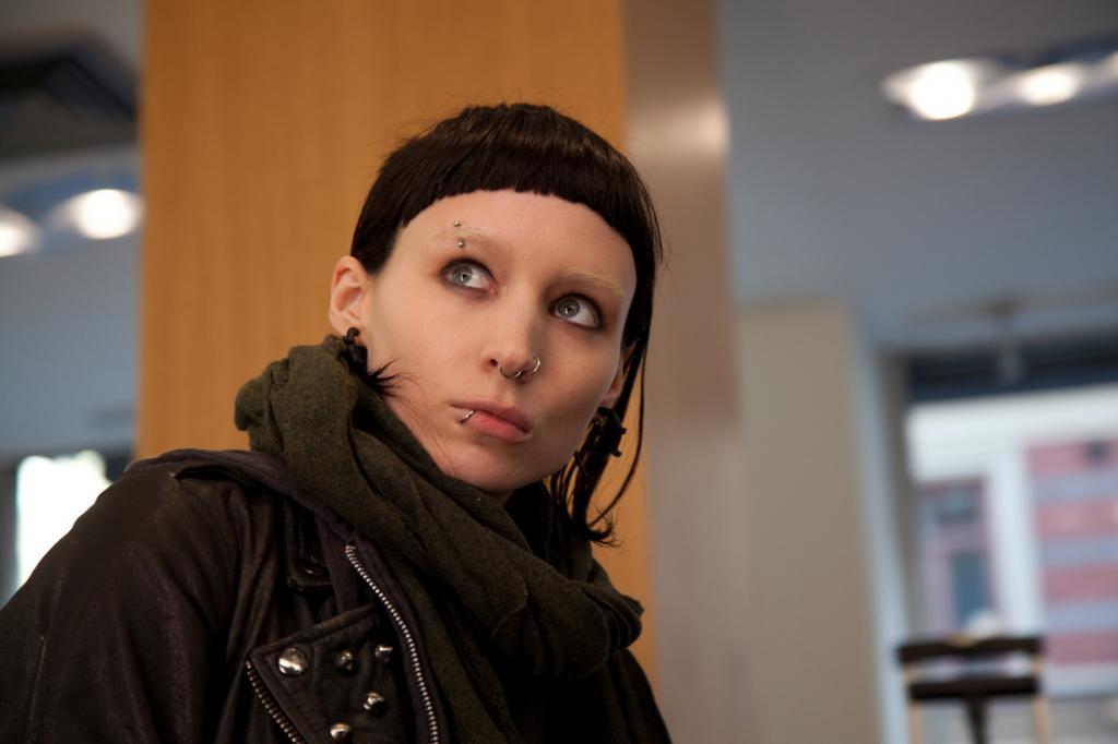 Для сьёмок в фильме «Девушка с татуировкой дракона» Руни Мара сделала пирсинг, как было положено по сценарию, за исключением губ и носа; актриса также изменила причёску и обесцветила брови. (Кадр из фильма)