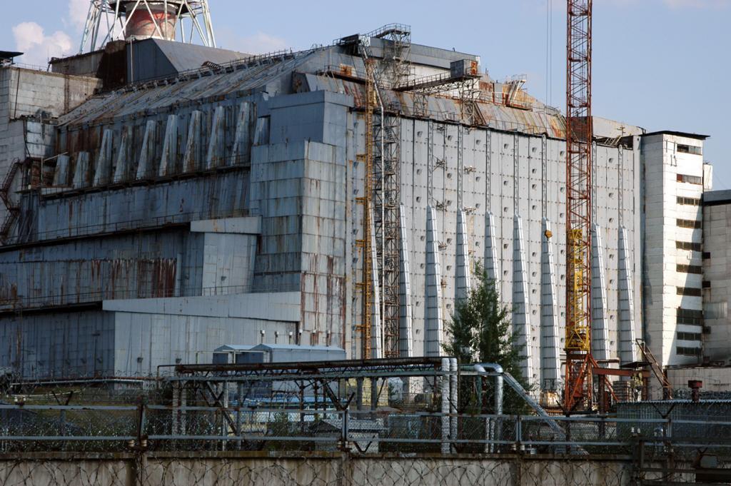 В целях предотвращения дальнейшего урона и защиты окружающей среды над четвёртым энергоблоком Чернобыльской атомной электростанции было возведено изоляционное сооружение — Саркофаг. Тем не менее, его «срок годности» всего 30 лет; после он становится непригодным для предотвращения дальнейших утечек радиации. Так что в запасе осталось совсем мало времени. (IAEA Imagebank)