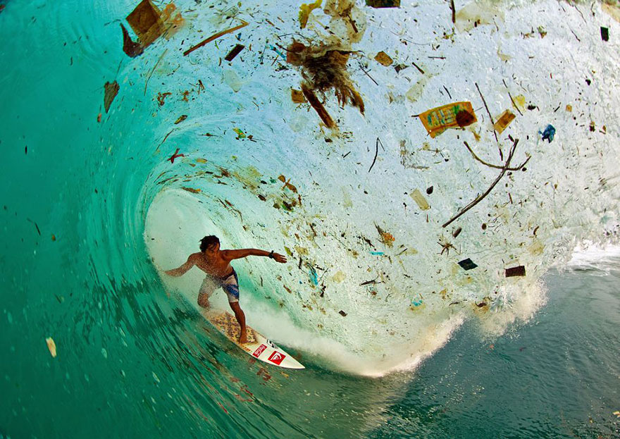 Сёрфер покоряет волну, полную мусора, у острова Ява — самого густонаселённого в мире.