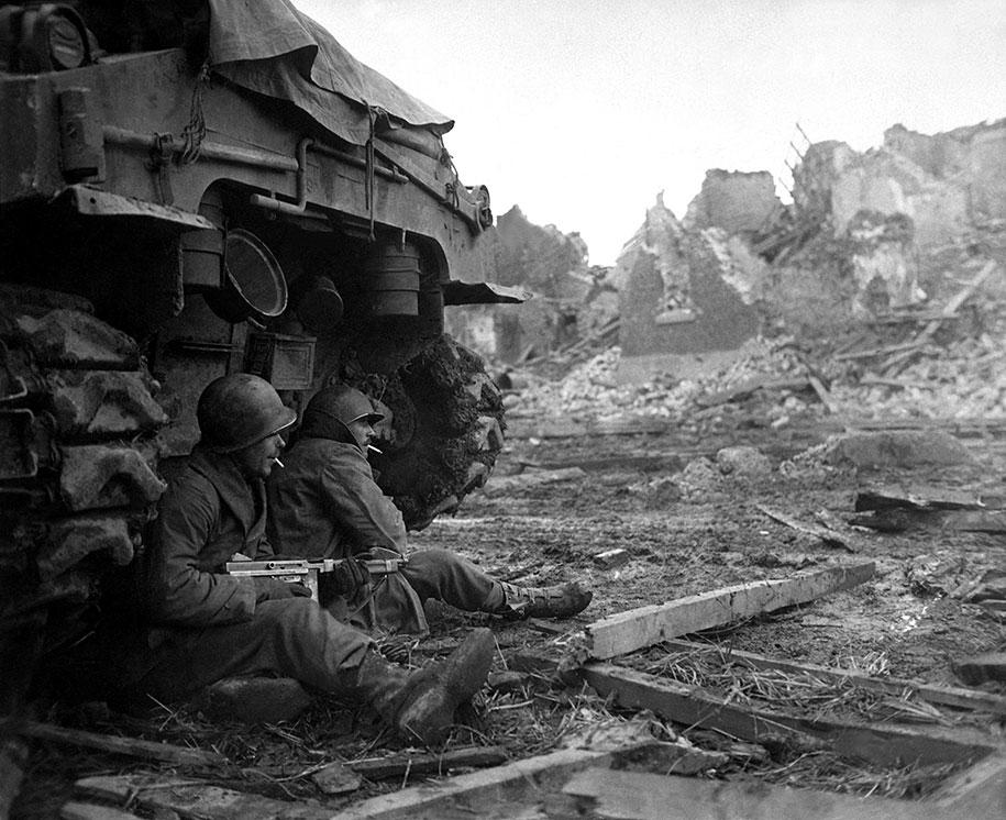 Двое американских солдат прячутся позади танка M4 Sherman, Германия, 1944 год