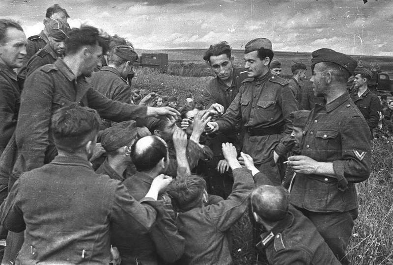 Советский солдат делится сигаретами с немецкими военнопленными, 1943 год.