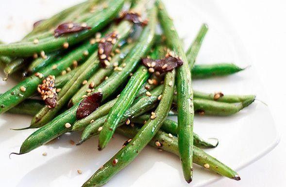 Возьмите полкилограмма зелёной фасоли, 2 чайных ложки оливкового масла и 1 чайную ложку кунжутного, чеснок, кунжут и соевый соус. Нагрейте большую кастрюлю или котелок на среднем огне. Налейте в него оливковое масло и добавьте нарезанный чеснок. Жарьте около минуты. Добавьте туда зеленую фасоль и кунжутное масло. Перемешайте и готовьте в течение 8-10 минут, пока фасоль не станет ярко-зеленой. Добавить соевый соус и часто помешивайте в течение 5 минут. Когда блюдо будет готово посыпьте его семенами кунжута.