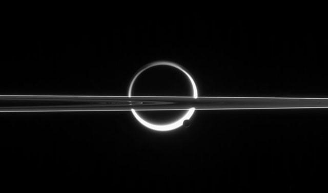 Кольца Сатурна, пересекающие Титан, недалеко от южного полюса которого виднеется Энцелад