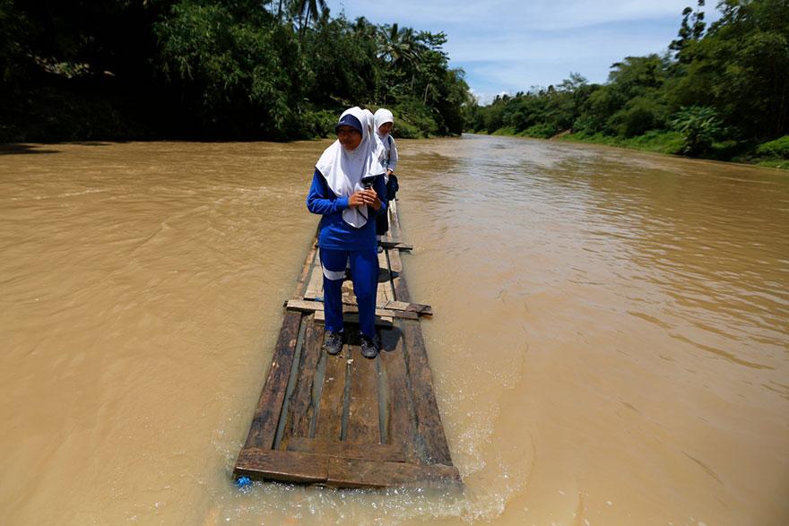 Дети преодолевают реку на бамбуковом плоту, Индонезия