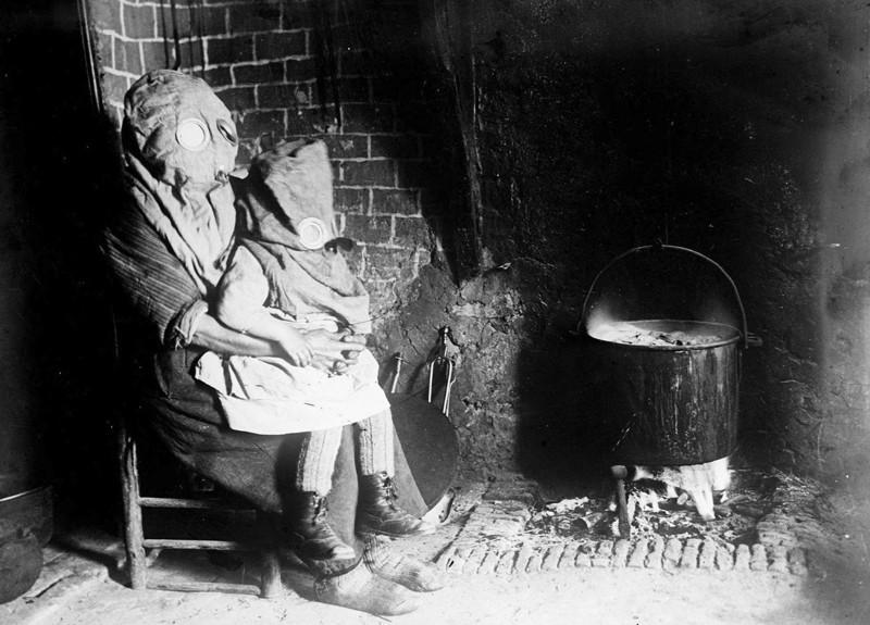 Мать с ребёнком готовят еду в противогазах. Французская глубинка, Первая мировая война.