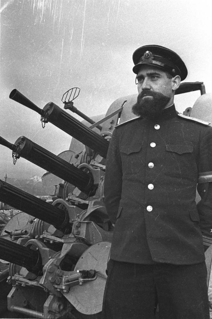 Советский вахтенный офицер в звании капитан-лейтенант на фоне 12,7-мм счетверённой корабельной зенитно-пулемётной установки «Виккерс».