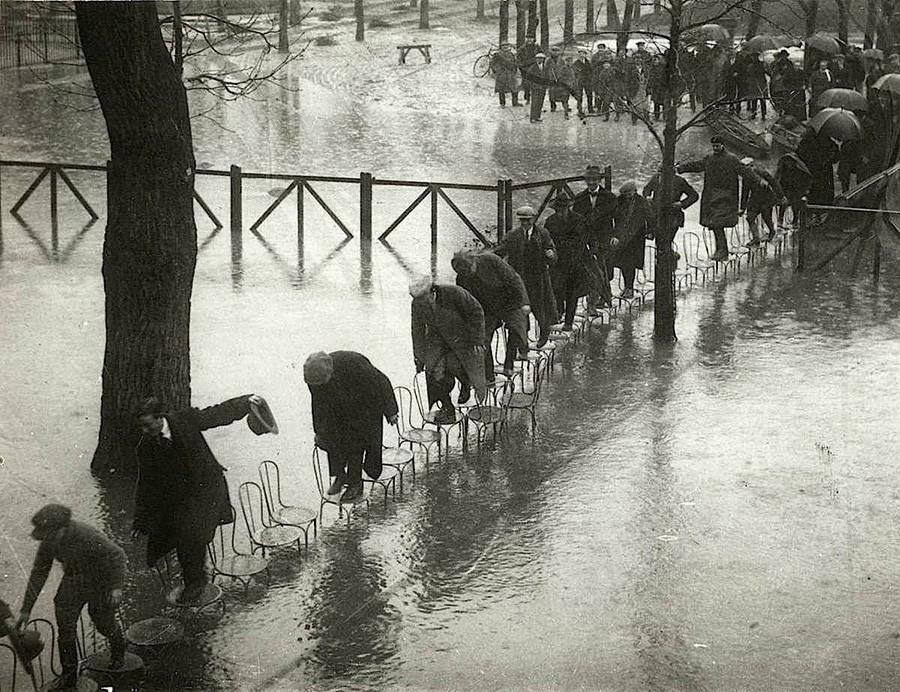 Парижане переходят затопленные улицы по стульям. 1924 год.