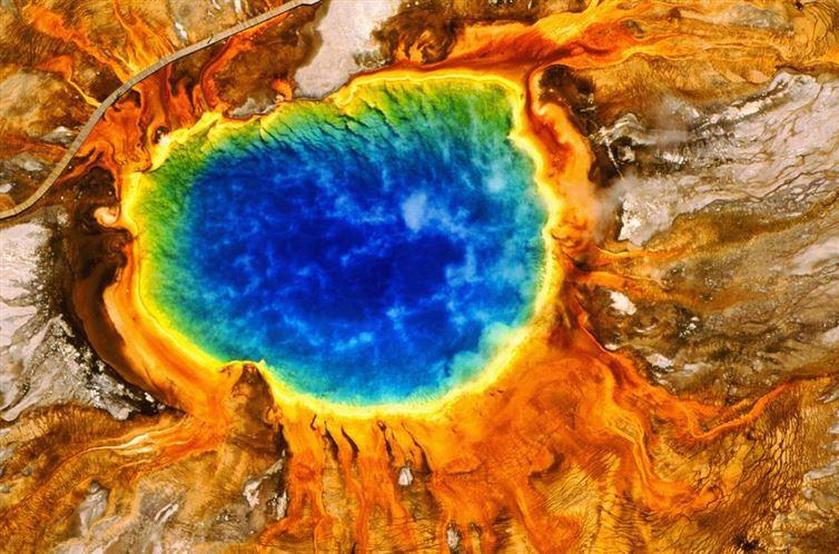 Это выглядит как краски, которые смешались на палитре, но на самом деле это Большой призматический источник в Йеллоустоунском национальном парке США. Палитра столь разнообразна благодаря различным бактериям; они живут в зонах различных температур.
