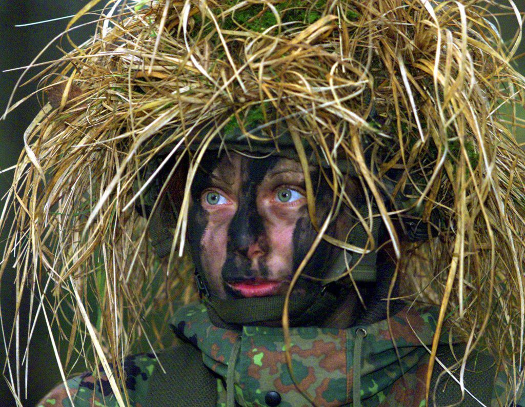 Private Dajana Bartczewski wears a full camouflage helmet and camouflage paint on her face during German army manuevers near Augustdorf, western Germany, 125 miles northeast of Duesseldorf, Tuesday, Jan. 9, 2001. It was the first time that female soldiers joined a military exercise in combat units and were permitted to handle weapons. The women joined the combat unit for the first time last Tuesday. (AP Photo/Frank Augstein)