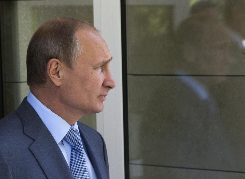 Путин смотрит на окно. Путин отметил отличную работу окна по отражению Путина в окне. (Sasha Mordovets/Getty Images)