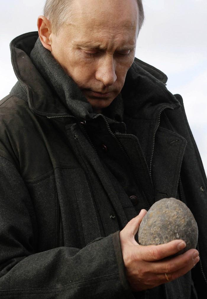 Путин смотрит на камень. Они немногословны. (RIA Novosti/Reuters)