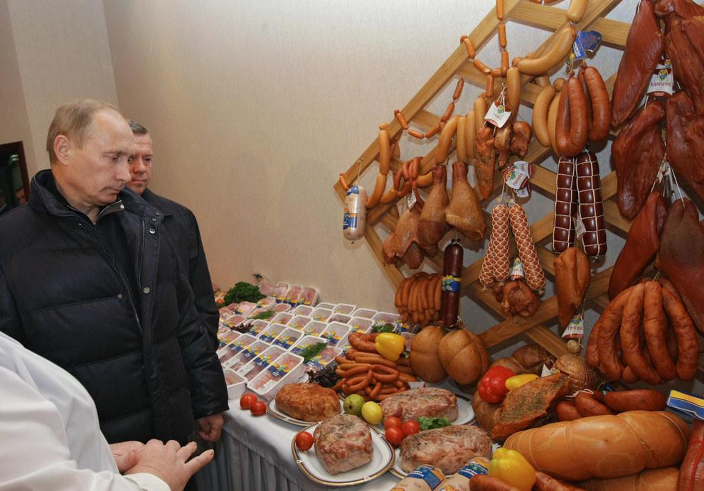 Путин смотрит на отечественные колбасы и немного грустит. (RIA Novosti/Reuters)