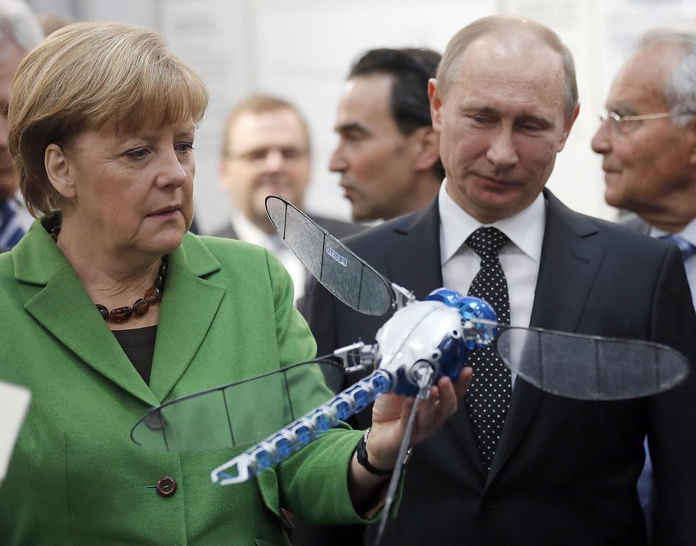 Путин и Ангела Меркель вместе смотрят на неопознанную летающую стрекозу. (AP Photo/Frank Augstein)