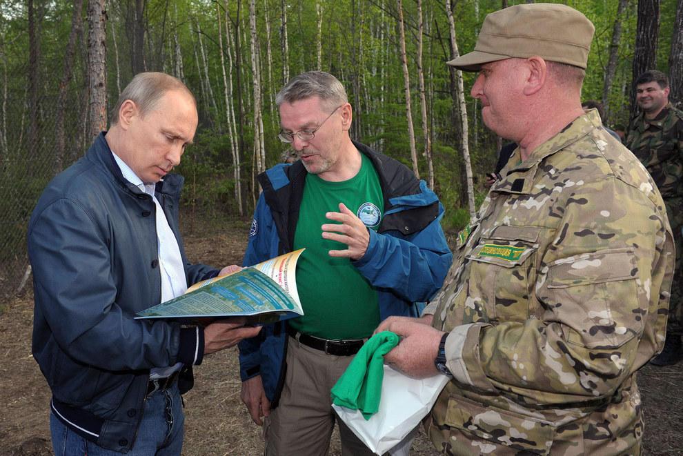 Путин смотрит в книгу. (RIA Novosti / Reuters)