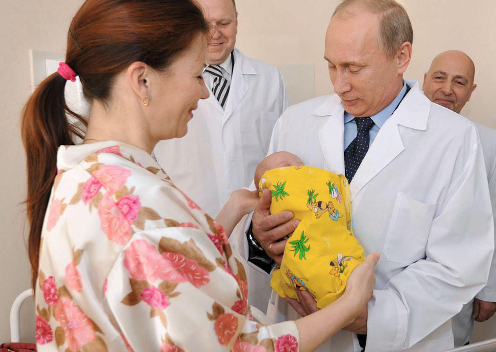 Путин смотрит на младенца. (RIA Novosti/Reuters)
