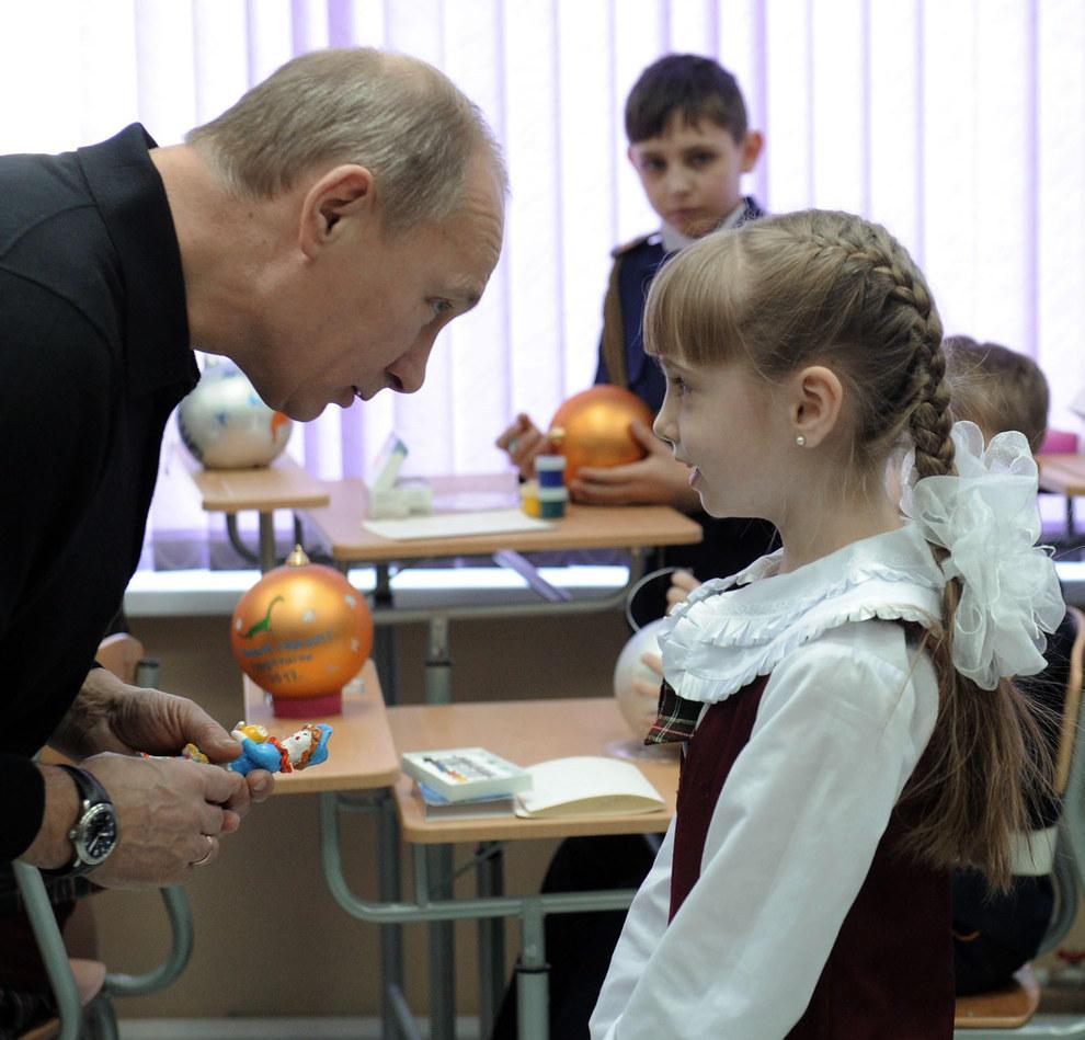 Путин смотрит на маленькую девочку. (RIA Novosti/Reuters)