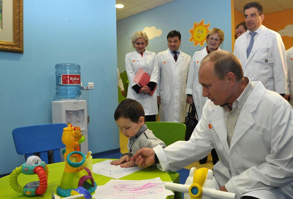 Путин смотрит на детские рисунки. (RIA Novosti/Reuters)