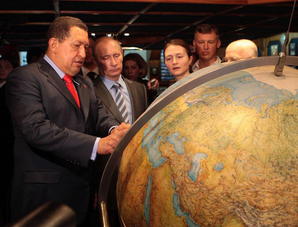 Путин смотрит на глобус и вспоминает свои оценки по географии. (Ho New/Reuters)