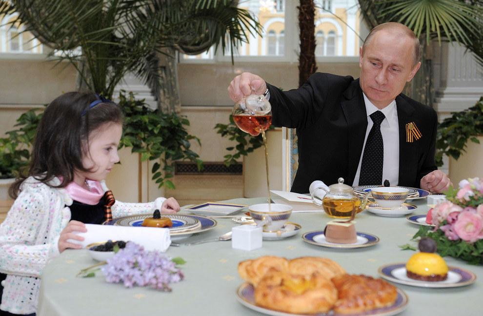 Путин смотрит на крошечный чайничек. (RIA Novosti/Reuters)