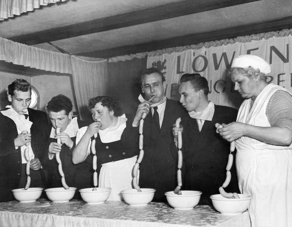 19 ноября 1952 года. Конкурс по поеданию сосисок в Мюнхене, Германия. Победитель (второй слева) съел 15 сосисок за 1 минуту и 45 секунд.