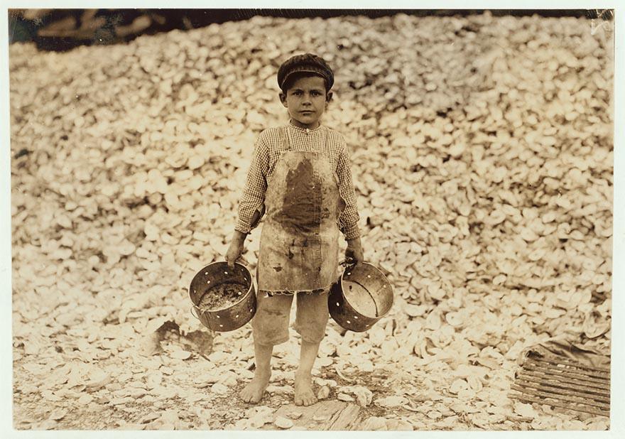 Пятилетний комплектовщик морепродуктов Мануэль. За спиной Мануэля гора устричных раковин, Билокси, штат Миссисипи.