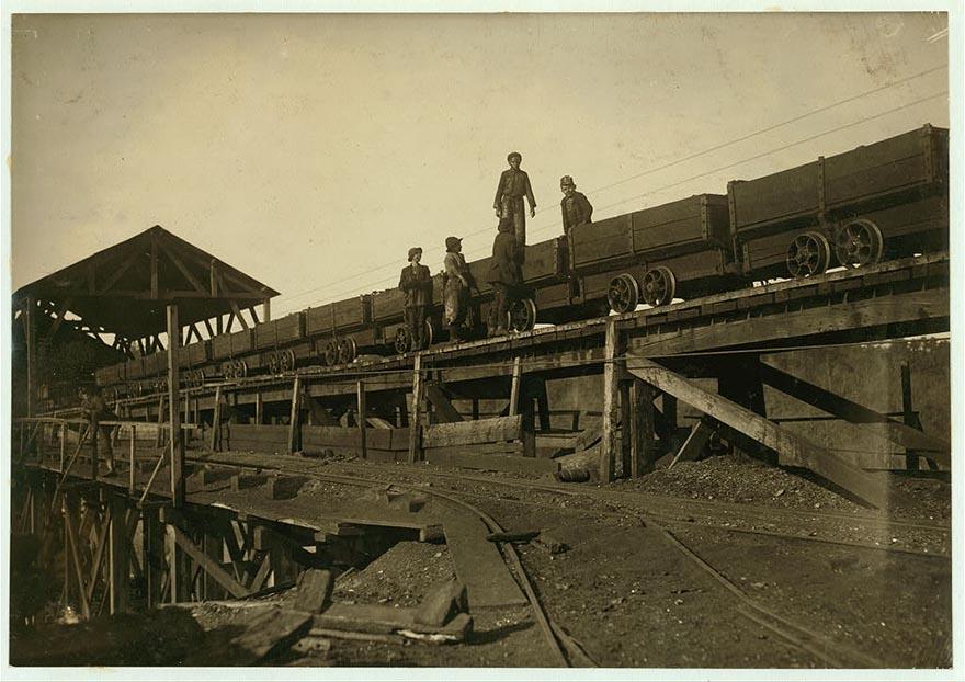 Мальчишки работают на движущихся платформах, которые перевозят уголь.